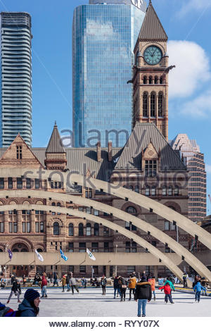 Skating in Nathan Phillips Square with old city hall recycled as a courthouse in background in Toronto Ontario Canada - Stock Image