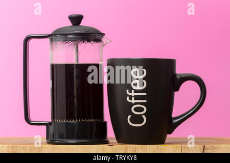 mug of coffee with a french press coffee pot - Stock Image