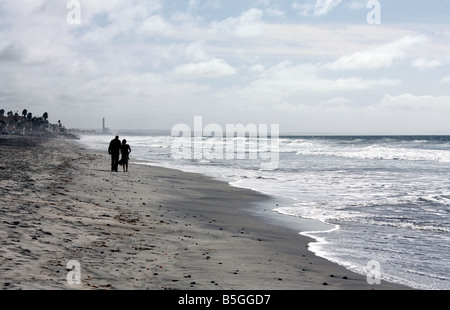 USA This couple enjoy a romatic walk on Oceanside Beach by the pier in Southern California - Stock Image