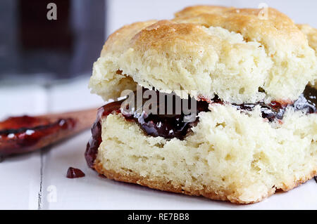 Buttermilk southern biscuit with raspberry or strawberry jam or jelly. Extreme shallow depth of field with selective focus on jam.. - Stock Image