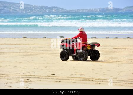 ATV quad bike being ridden by an RNLI  lifeguard,Riviere Towans beach,Riviere Towans beach, Phillack, Hayle,cornwall,England,UK - Stock Image