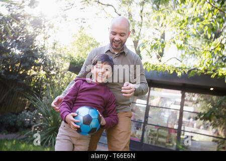 Father and son playing with soccer ball in backyard - Stock Image