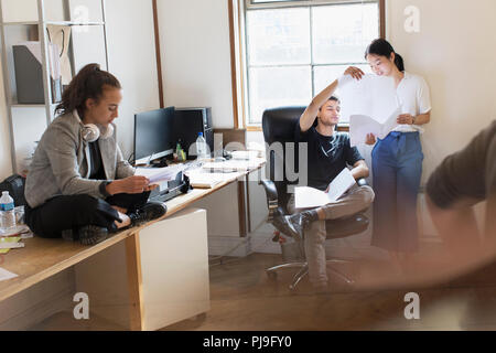 Creative business people discussing paperwork in office - Stock Image