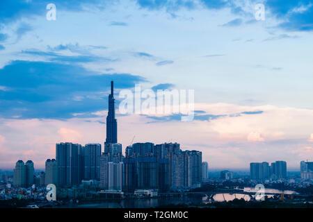 Modern highrise buildings and cranes beside Siagon River at dusk. Ho Chi Minh City (Saigon), Vietnam, Asia - Stock Image