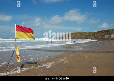 A red and yellow RNLI beach safety flag flying on Crooklets Beach denoting an area patrolled by lifeguards. - Stock Image