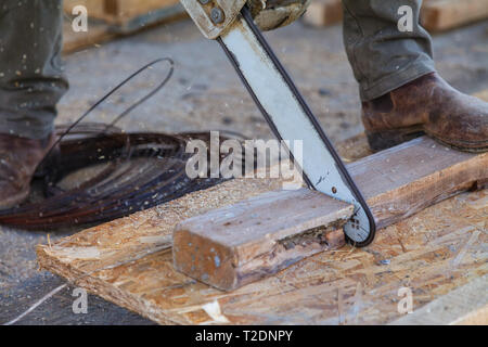 A man using a chainsaw saws a wooden beam - Stock Image