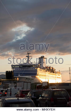 Vehicles Waiting To Board Cross Channel Ferry Docked In Portsmouth Harbour At Sunset - Stock Image