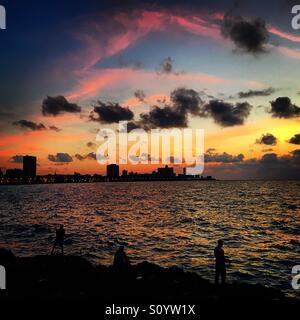 Fishermen at sunset along the Malecon in Havana Cuba - Stock Image