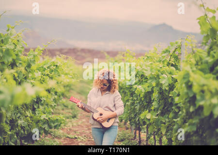 outdoor lady playing an acoustic ukulele guitar in the vineyard. artist at work creating a new song and enjoying the leisure activity with music. beau - Stock Image