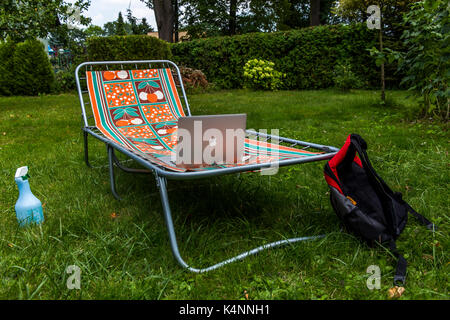Sunbed on the grass with apple macbook on it and a bag. - Stock Image