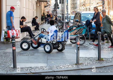 Berlin street view, young boy with pedal car,woman with pram,people walking. people sitting,apartment buildings - Stock Image