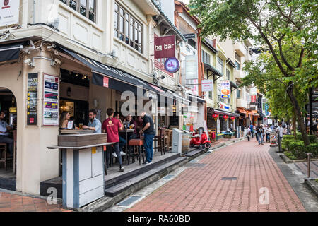 Singapore - 14th December 2018: People drinking in pubs on Boat Quay. The street is popular with both tourists and expats. - Stock Image