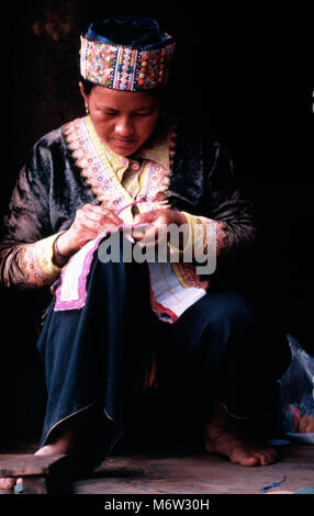 An indigenous H'mong hilltibe seamstress making traditional clothes by hand in her village in northern Thailand. - Stock Image