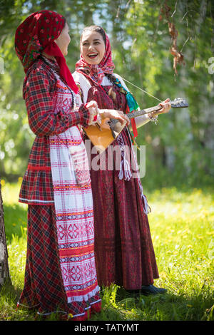 Two young woman in traditional russian clothes standing in the forest and look at each other. One of them playing balalaika and sing - vertical shot - Stock Image