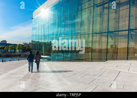 Oslo summer, rear view in summer of a tourist couple descending the vast access ramp leading to the roof of the Oslo Opera House, Norway. - Stock Image