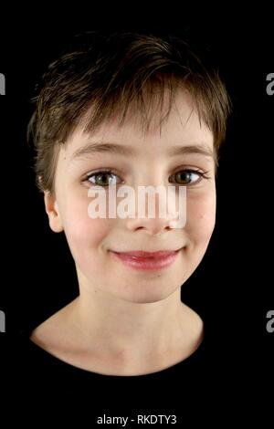 Portrait of a smiling child with a pixie haircut against a black background - Stock Image