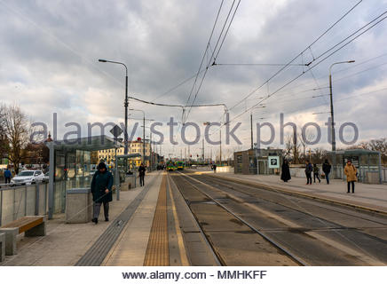 People waiting at the Kaponiera public transport stop for the tram on a cloudy day in Poznan, Poland - Stock Image