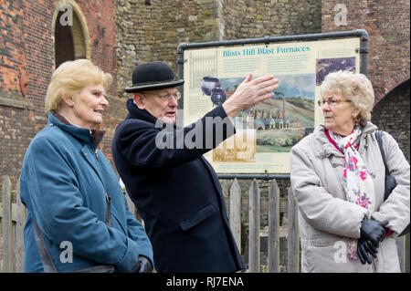Volunteer male guide, dressed in Victorian costume, directs two senior lady visitors to Blists Hill Victorian Town, Shropshire, UK - Stock Image