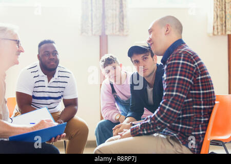 Attentive men talking and listening in group therapy - Stock Image