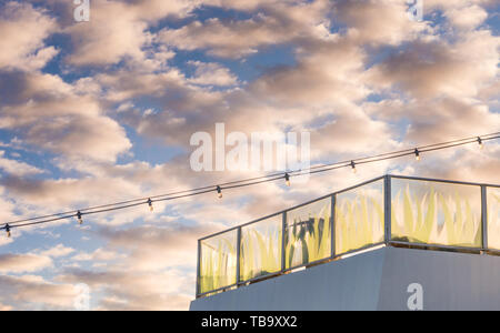 Stern Lido deck glass paned balcony and light string at sunrise on cruise ship. - Stock Image