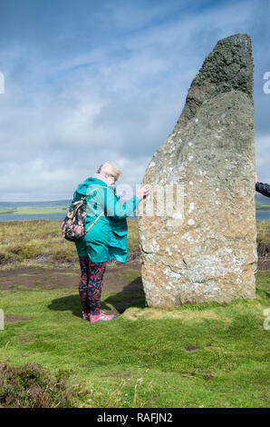 Tourist standing by the Ring of Brodgar Neolithic henge and stone circle near Stromness on the Orkney Islands, Scotland. - Stock Image