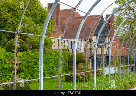 The manor house at RHS Wisley seen through a plant climbing frame - Stock Image
