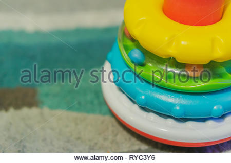 Close up of colorful plastic stacking toy rings on a carpet. - Stock Image