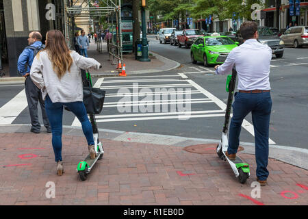 CHARLOTTE, NC, USA-11/08/18: A man and woman on electric scooters, waiting to cross a street. - Stock Image