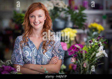 Happy female florist standing with arms crossed in flower shop - Stock Image