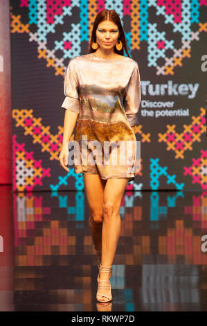 Turkish designs on the Main Catwalk, Pure London AW19, Kensington Olympia, London, UK. Autumn/Winter 2019 collections were on show at Pure London. Fashion buyers flocked to Olympia, 10th-12th February, where a wide range of brands exhibited their latest designs across womenswear, menswear, childrenswear, and accessories. Catwalk shows and seminars by industry experts took place throughout the day to complete the experience. 12th February 2019. Credit: Antony Nettle/Alamy Live News - Stock Image