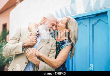 Happy fashion senior couple dating outdoor - Mature elegant older people celebrating date of their anniversary - Wife kissing her husband - Stock Image