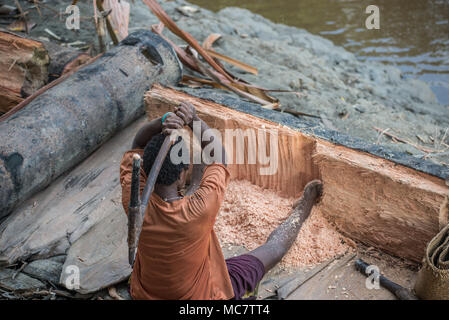 A woman scraping a sago palm trunk with an axe, Swagup village, Upper Sepik, papua New Guinea - Stock Image