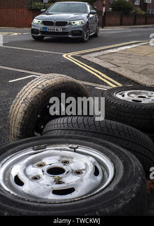 Car driving past, a pile of discarded, car tyres, illegally fly tipped discarded tyres - Stock Image