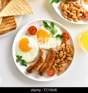 Tasty breakfast with fried eggs, sausages, beans, tomatoes, greens on plate over white stone background. Top view, flat lay - Stock Image