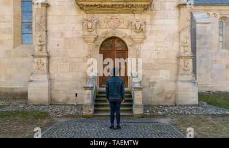 A tourist young man standing against a beautiful old medieval chatedral door. A man  in front of a an old architecture church entrance door in Alba Iu - Stock Image