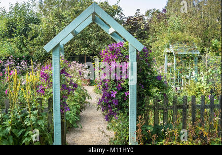 Cottage style garden with archway, August, Barnsdale, England, UK - Stock Image