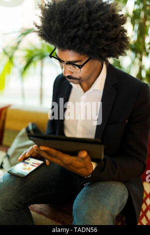 Businessman sitting on bench using tablet and cell phone - Stock Image