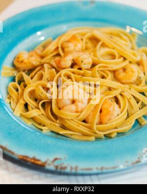 Shrimp scampi over fetticchini pasta served on an aqua plate. - Stock Image
