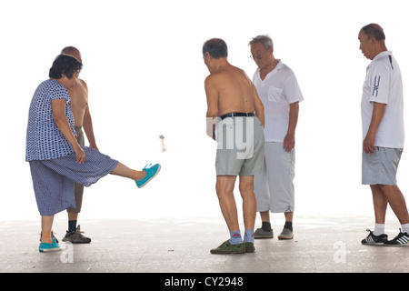 Pensioners kicking around a large shuttlecock in Shuishang Park, Tianjin, China. - Stock Image