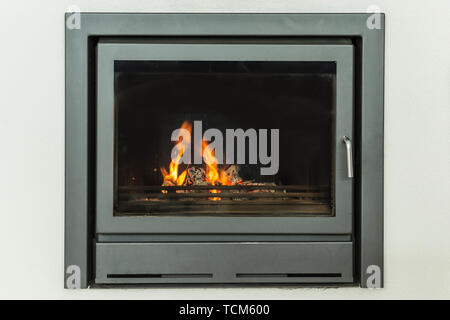 Luxurious modern design fireplace burning firewood, door with fire resistant glass window. Home interior with white walls on yellow marble floor - Stock Image