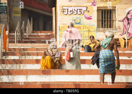 Some Sadhus and Hindu people are relaxing and walking on a Ghat in Varanasi. Sadhu is an ascetic or someone who practice yoga. - Stock Image