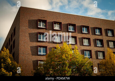 Corner and edge of the red brick building with blue sky in a background and autumn trees with yellow leaves in a foreground in Hamburg, Germany - Stock Image