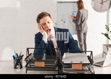 selective focus of tired man yawning near document trays with lettering with female coworker on background, procrastination concept - Stock Image