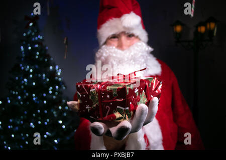 Point of view of santa handing over a christmas gift in foreground and in focus with father christmas in background and blurred. - Stock Image