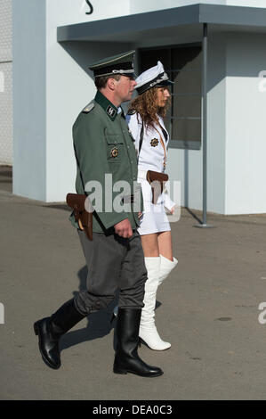 Chichester, West Sussex, UK. 14th Sep, 2013. Goodwood Revival. Goodwood Racing Circuit, West Sussex - Saturday 14th September. A couple dressed in uniform walk through the revival festival. The man is typical  uniform whist his female companion is sporting a white hat, jacket, mini-skirt and thick length white high heeled boots. Credit:  MeonStock/Alamy Live News - Stock Image