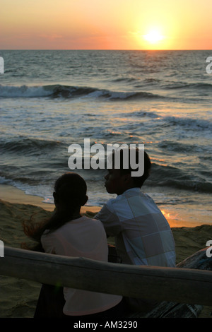 Couple sitting on a boat at sunset Negombo beach Sri Lanka - Stock Image