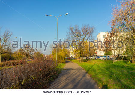 Poznan, Poland - November 7, 2018: Footpath along trees and apartment buildings on the Inflancka street. - Stock Image