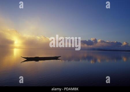 Fishing boat, silhouette of canoe in sunrise, quiet sea landscape, morning mist dissipating. Bahia State, Brazil. - Stock Image
