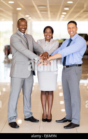 multiracial car dealership staff putting their hands together - Stock Image