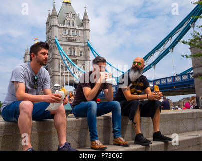 London, England. 4th July 2018. Klaus, Will and Mitul take time out of their busy day at their Design company to eat lunch on a very hot day near London'd Tower Bridge. The present heatwave is set to continue. ©Tim Ring/Alamy Live News - Stock Image